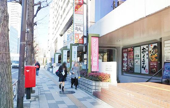 5.左手にポスト、右手に大きなビルがあり、居酒屋、飲食店の看板が見えます。